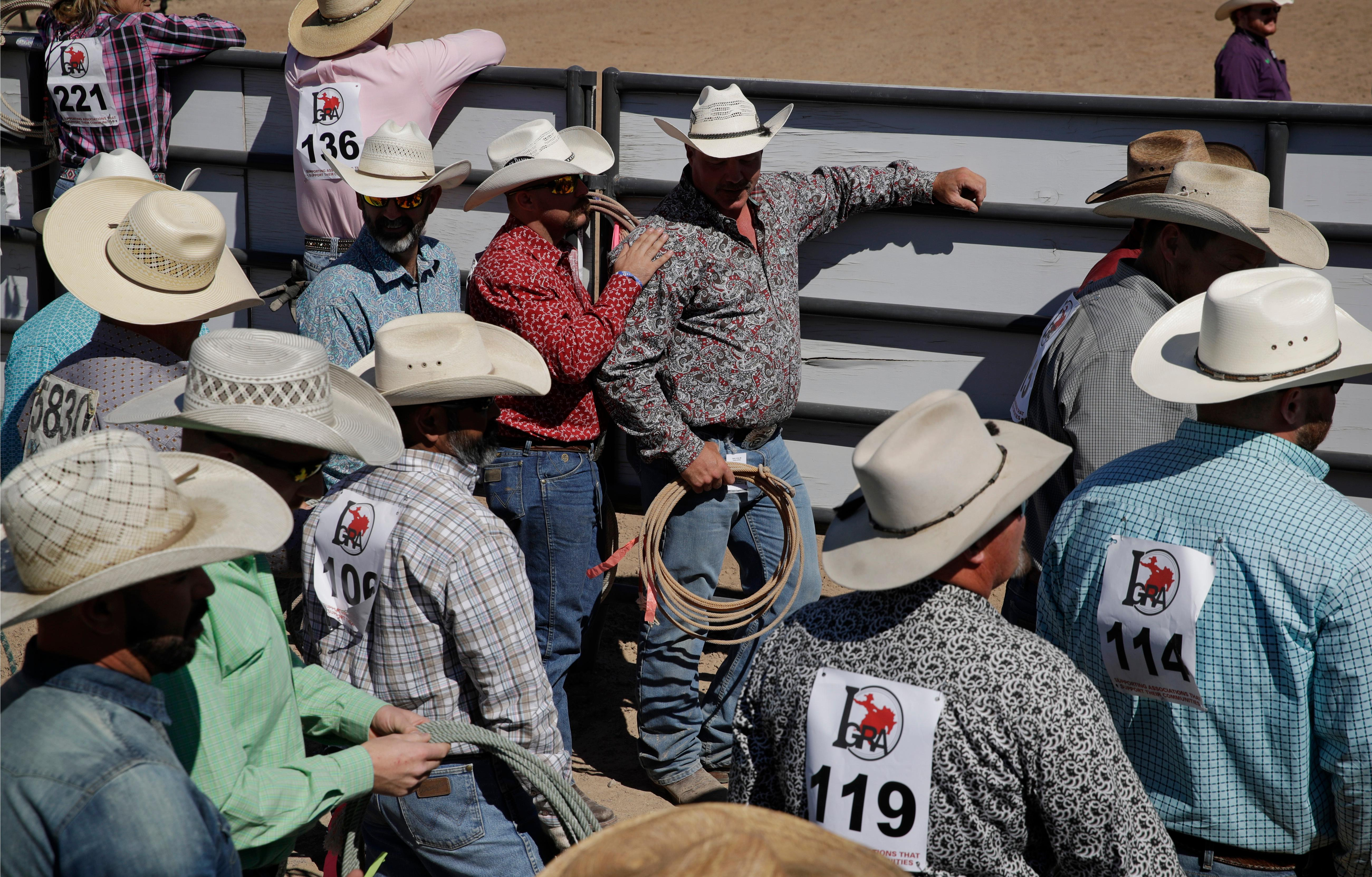 In this Sept. 24, 2017, photo, competitors wait to compete in the calf roping on foot event at the Bighorn Rodeo in Las Vegas. Circuit rodeos feature a variety of traditional events, including bull riding, bareback bronc riding, calf roping and barrel racing. (AP Photo/John Locher)