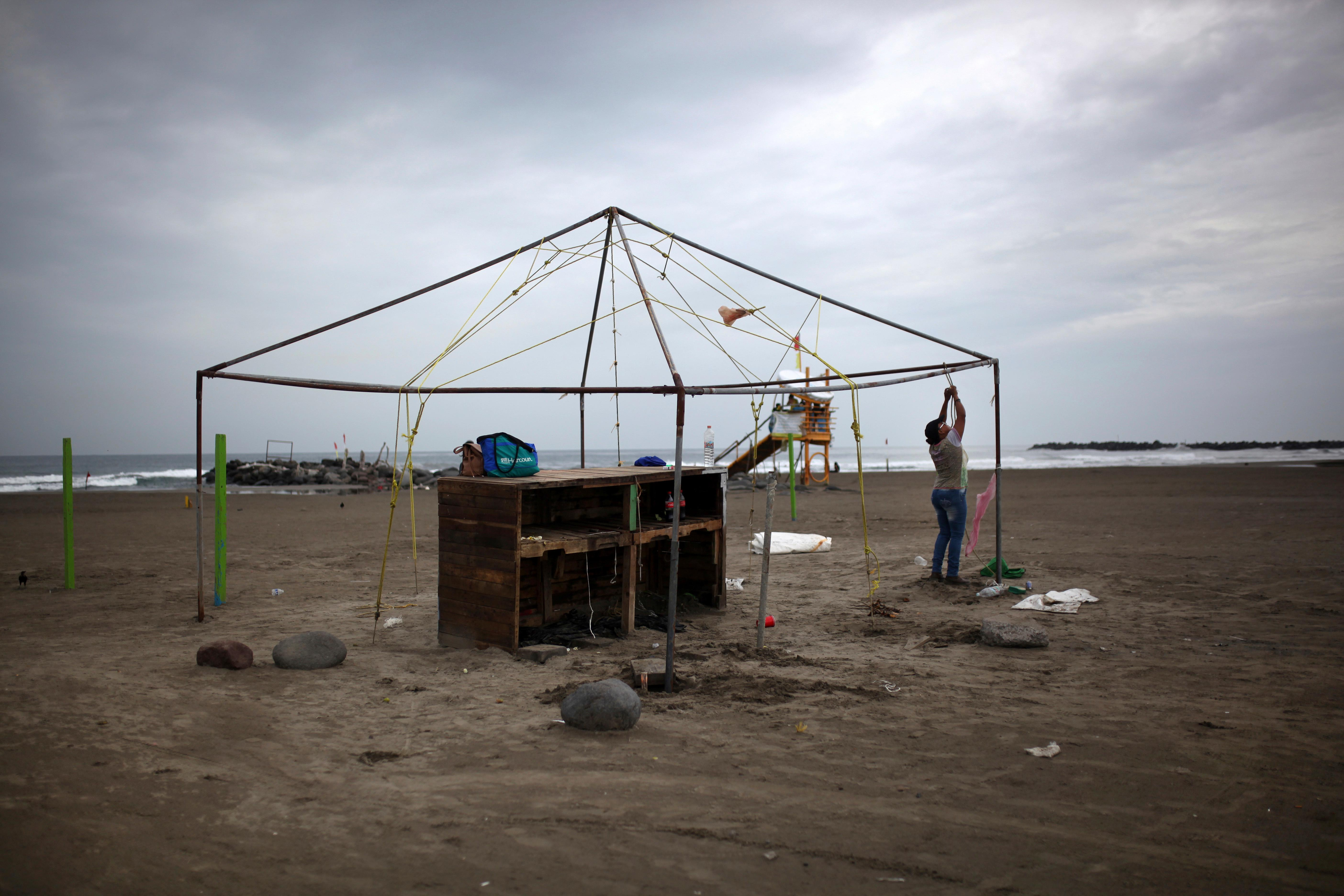 A woman ties down the frame of a beachfront business as she prepares for the arrival of Tropical Storm Franklin, in the port city of Veracruz, Mexico, Wednesday, Aug. 9, 2017. A strengthening Tropical Storm Franklin took aim at Mexico's central Gulf coast after a relatively mild run across the Yucatan Peninsula, with forecasts saying it would grow into a hurricane before making its second landfall late Wednesday or early Thursday. (AP Photo/Felix Marquez)