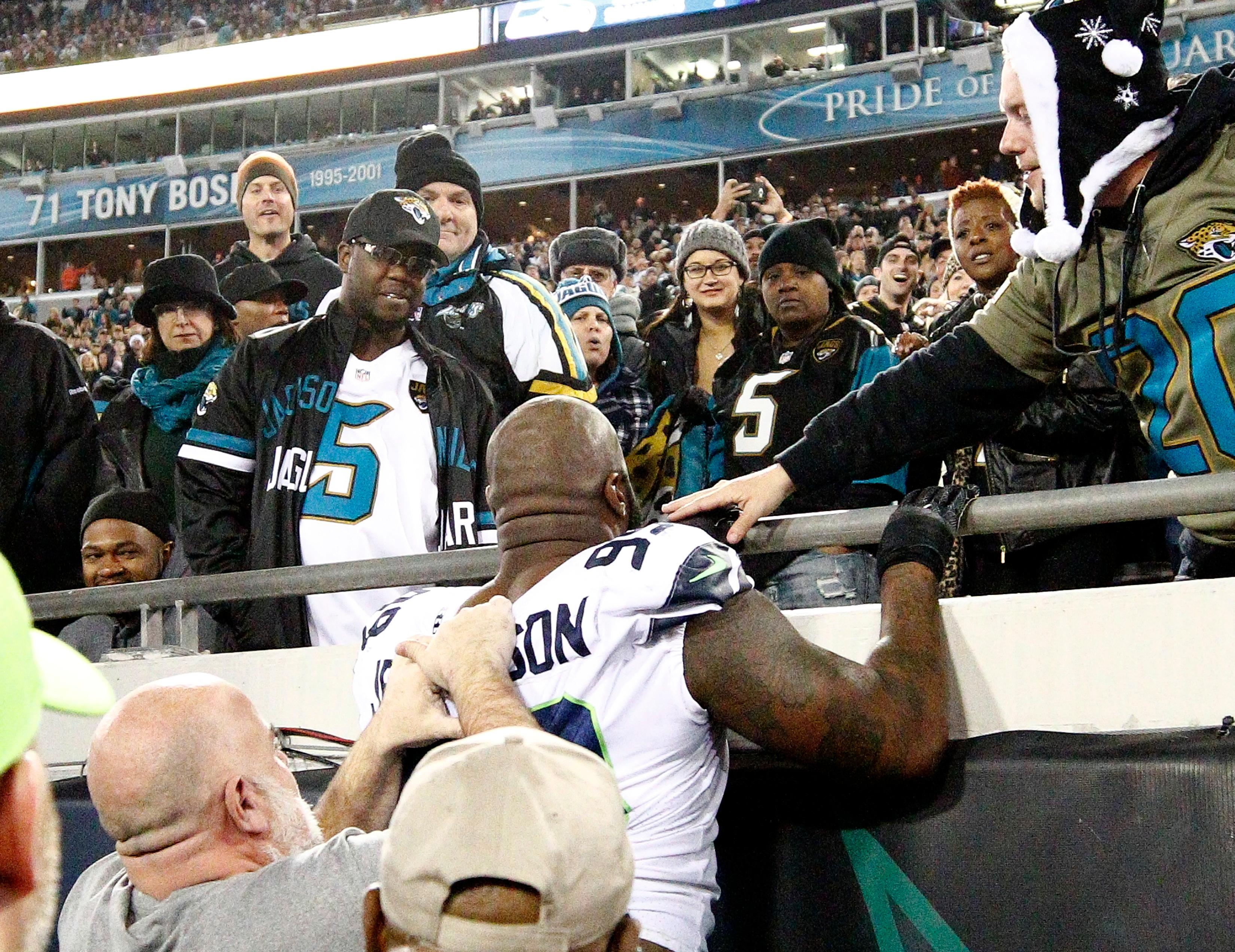 Seattle Seahawks defensive tackle Quinton Jefferson, center, tries to climb up in the stands after Jacksonville Jaguars fans threw objects at him in the closing moments of an NFL football game, Sunday, Dec. 10, 2017, in Jacksonville, Fla. Jacksonville won 30-24. (AP Photo/Stephen B. Morton)