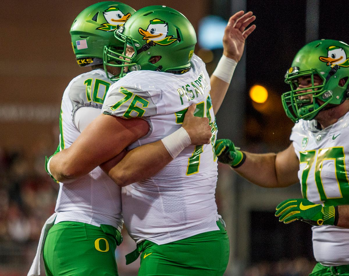 Oregon Ducks quarterback Justin Herbert (#10) receives hugs and highfives from Jake Pisarcik (#76) and Zac Morgan (#70) after scoring a touchdown against the Washington State Cougars late in the fourth quarter. The Cougars beat the Ducks 51-33 at Martin Stadium on Saturday evening. Photo by Katie Pietzold