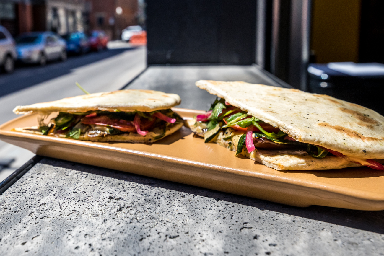 Veggie Sandwich: roasted eggplant and zucchini, Lost & Found hummus, pickled red onion, tomato, arugula, and Manchego cheese served on house-made pita bread / Image: Catherine Viox{ }// Published: 5.16.20