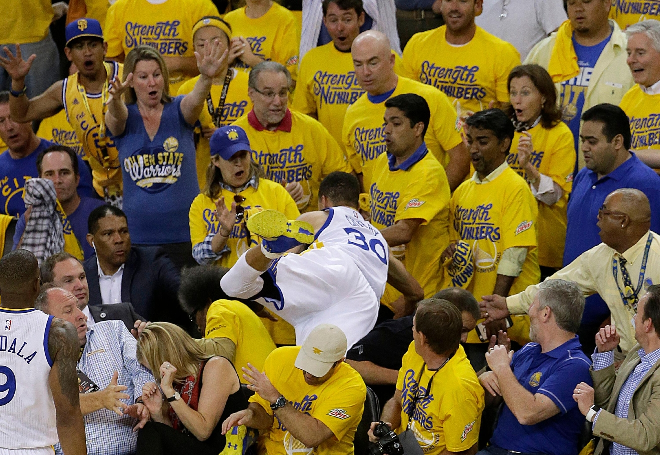 Golden State Warriors guard Stephen Curry (30) falls over a row of fans while chasing a loose ball during the first half of Game 2 of the NBA basketball Western Conference finals against the Oklahoma City Thunder in Oakland, Calif., Wednesday, May 18, 2016. (AP Photo/Jeff Chiu)