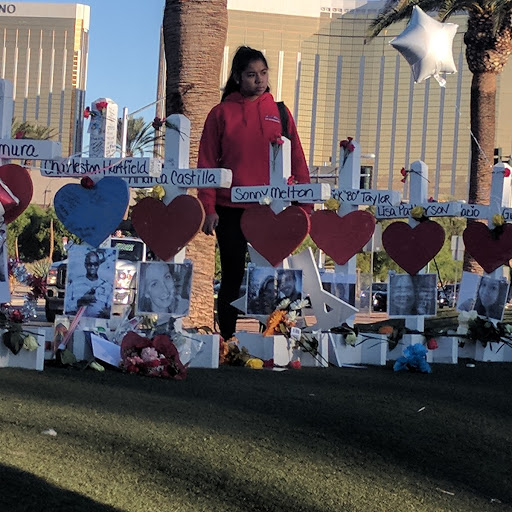 A visitor inspects the 58 crosses lining the green immediately north of the Welcome to Las Vegas sign near Mandalay Bay (background) on Friday, Oct. 7, 2017. (Marvin Clemons | KSNV)<p></p>
