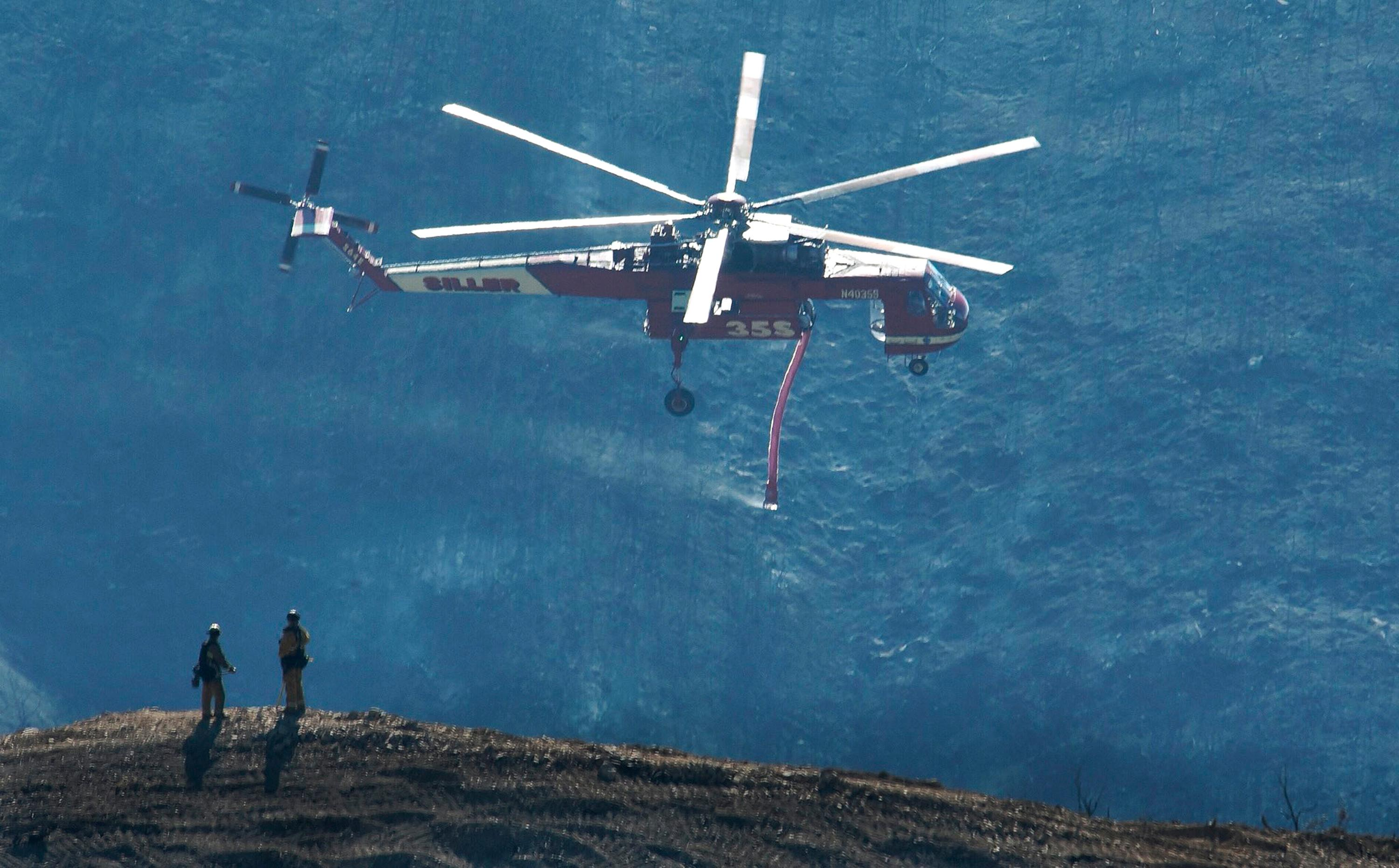 In this photo provided by the Santa Barbara County Fire Department, a Skycrane helicopter passes firefighters atop a hillside while coming in for a water drop below E. Camino Cielo in Santa Barbara, Calif., Tuesday, Dec. 19, 2017. Although some evacuations were lifted Monday and more residents were being allowed to return Tuesday, hillside homes are still threatened in Santa Barbara, where firefighters mounted an aggressive air attack on stubborn flames. Officials estimate that the Thomas Fire will grow to become the biggest in California history before full containment, expected by Jan. 7, 2018. (Mike Eliason/Santa Barbara County Fire Department via AP)
