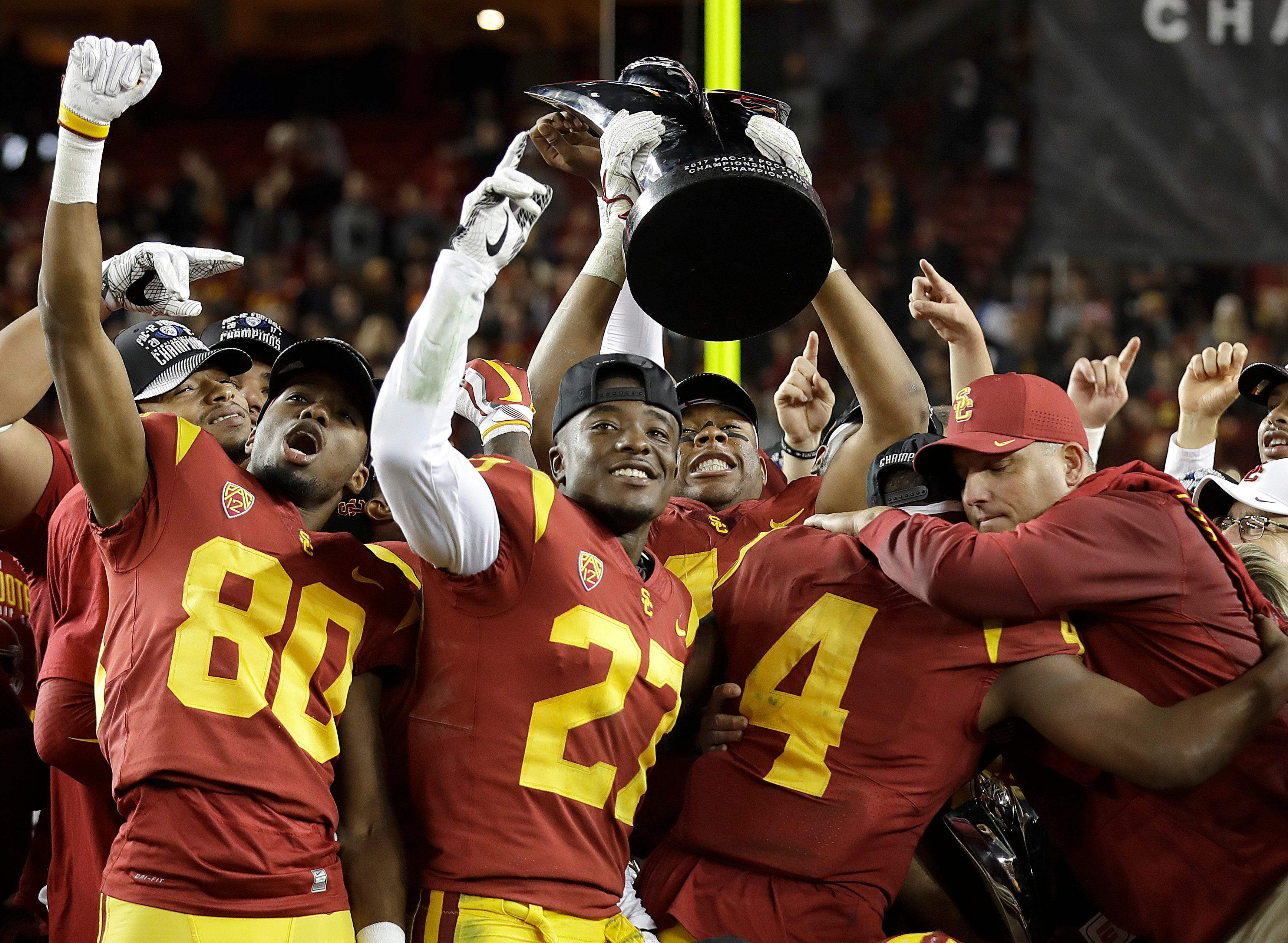 Southern California coach Clay Helton, right, celebrates with players after a 31-28 win over Stanford in the Pac-12 Conference championship NCAA college football game in Santa Clara, Calif., Friday, Dec. 1, 2017. (AP Photo/Marcio Jose Sanchez)