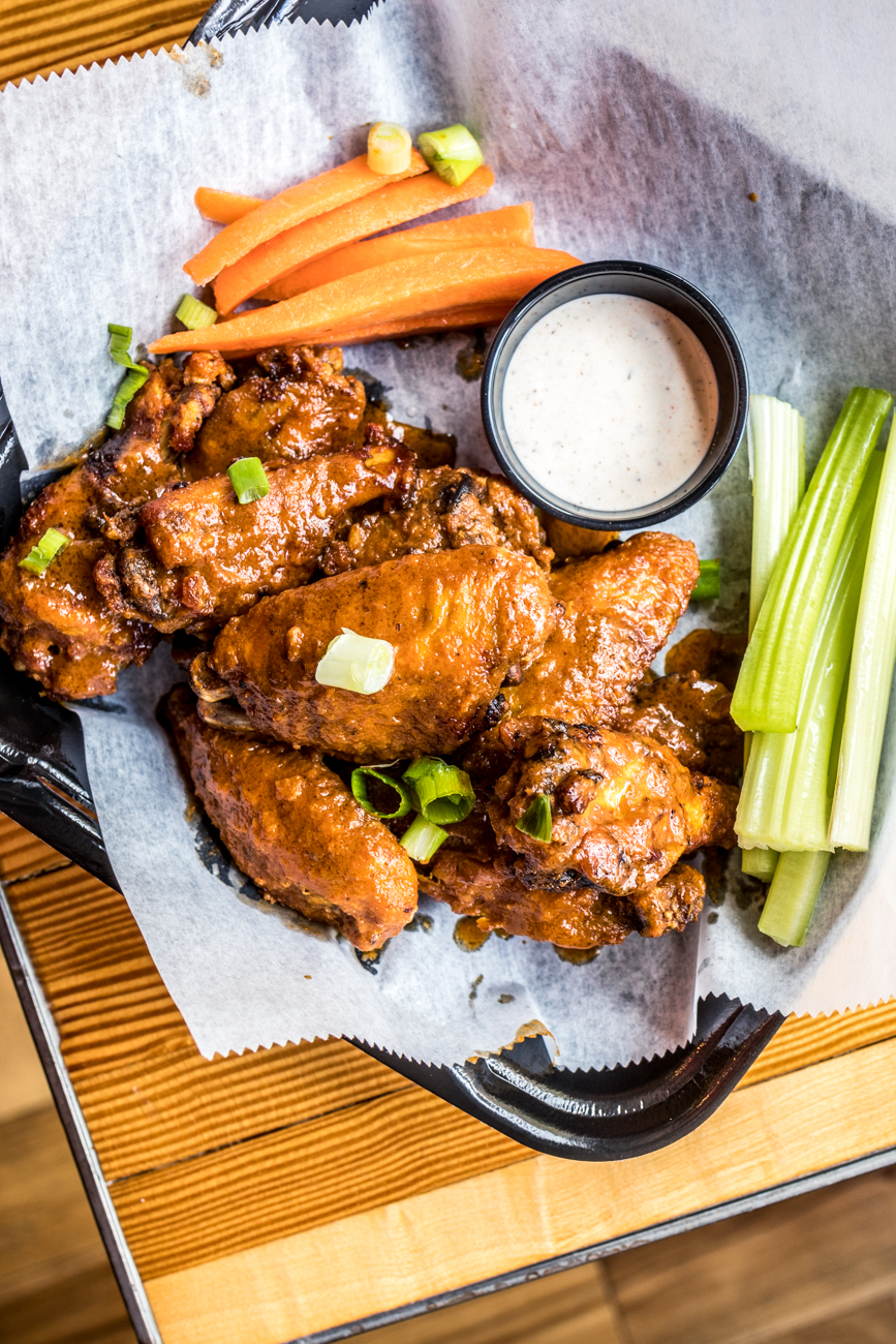 """Buffalo"" Wings: fried jumbo wings brined with Buffalo Trace and tossed in sweet & spicy classic buffalo or BBQ sauce and served with carrots, celery, and ranch dressing / Image: Catherine Viox // Published: 5.18.20"