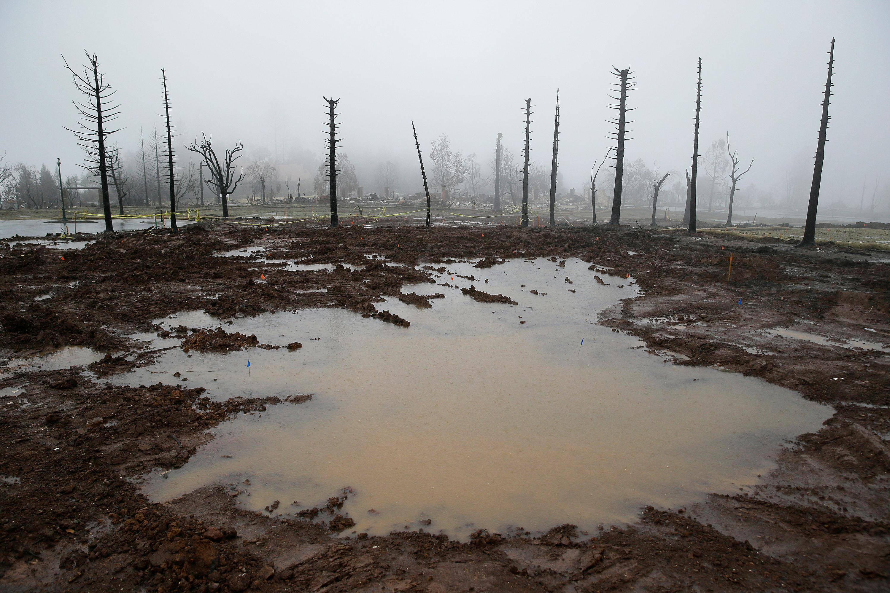 Rain water pools where a Fountaingrove neighborhood home once stood Monday, Jan. 8, 2018, in Santa Rosa, Calif. Storms brought rain to California on Monday and increased the risk of mudslides in fire-ravaged communities in devastated northern wine country and authorities to order evacuations farther south for towns below hillsides burned by the state's largest-ever wildfire. (AP Photo/Eric Risberg)