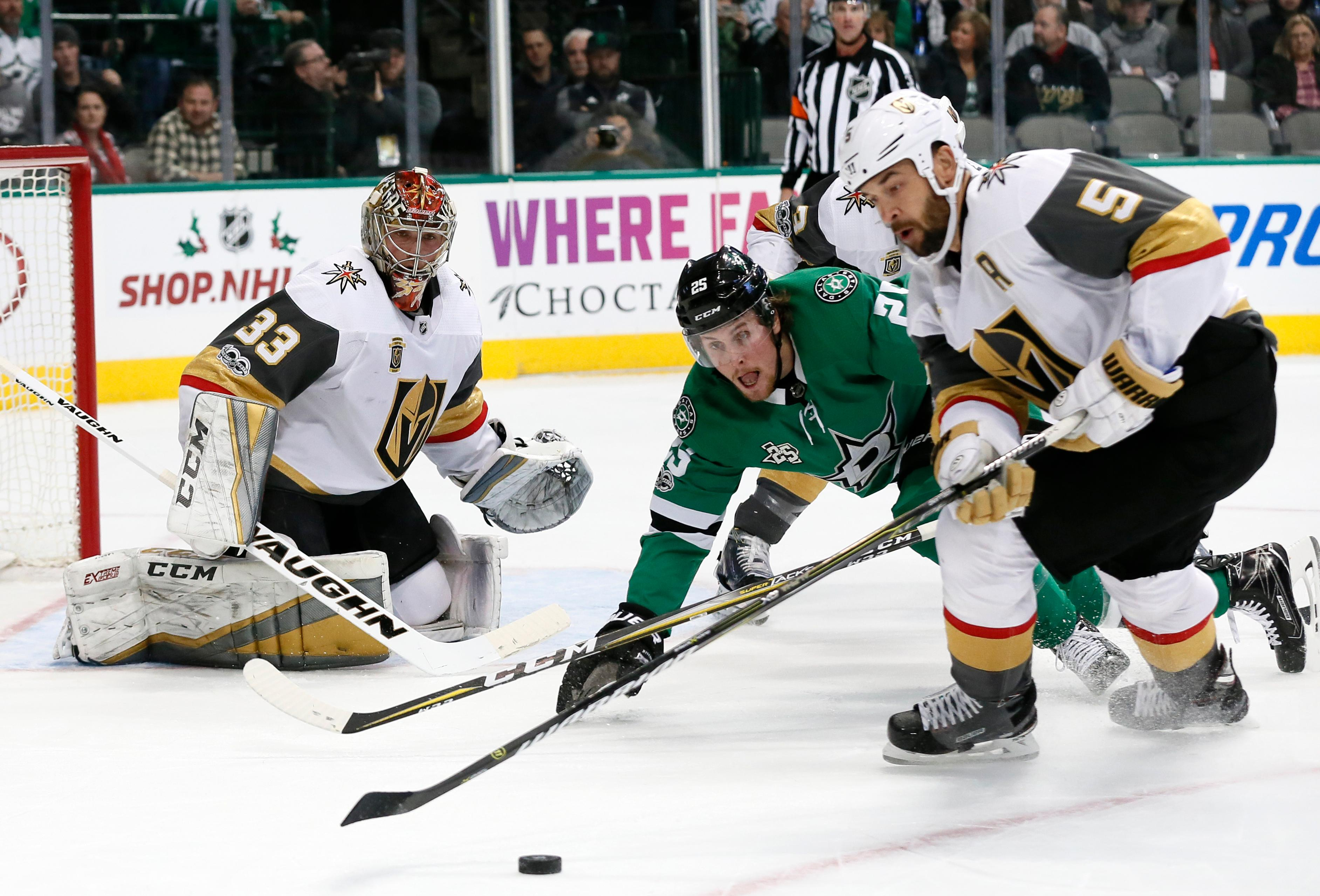Vegas Golden Knights' Maxime Lagace (33) and Dallas Stars right wing Brett Ritchie (25) watch as defenseman Deryk Engelland (5) clears a puck from in front of the net during the first period of an NHL hockey game, Saturday, Dec. 9, 2017, in Dallas. (AP Photo/Tony Gutierrez)