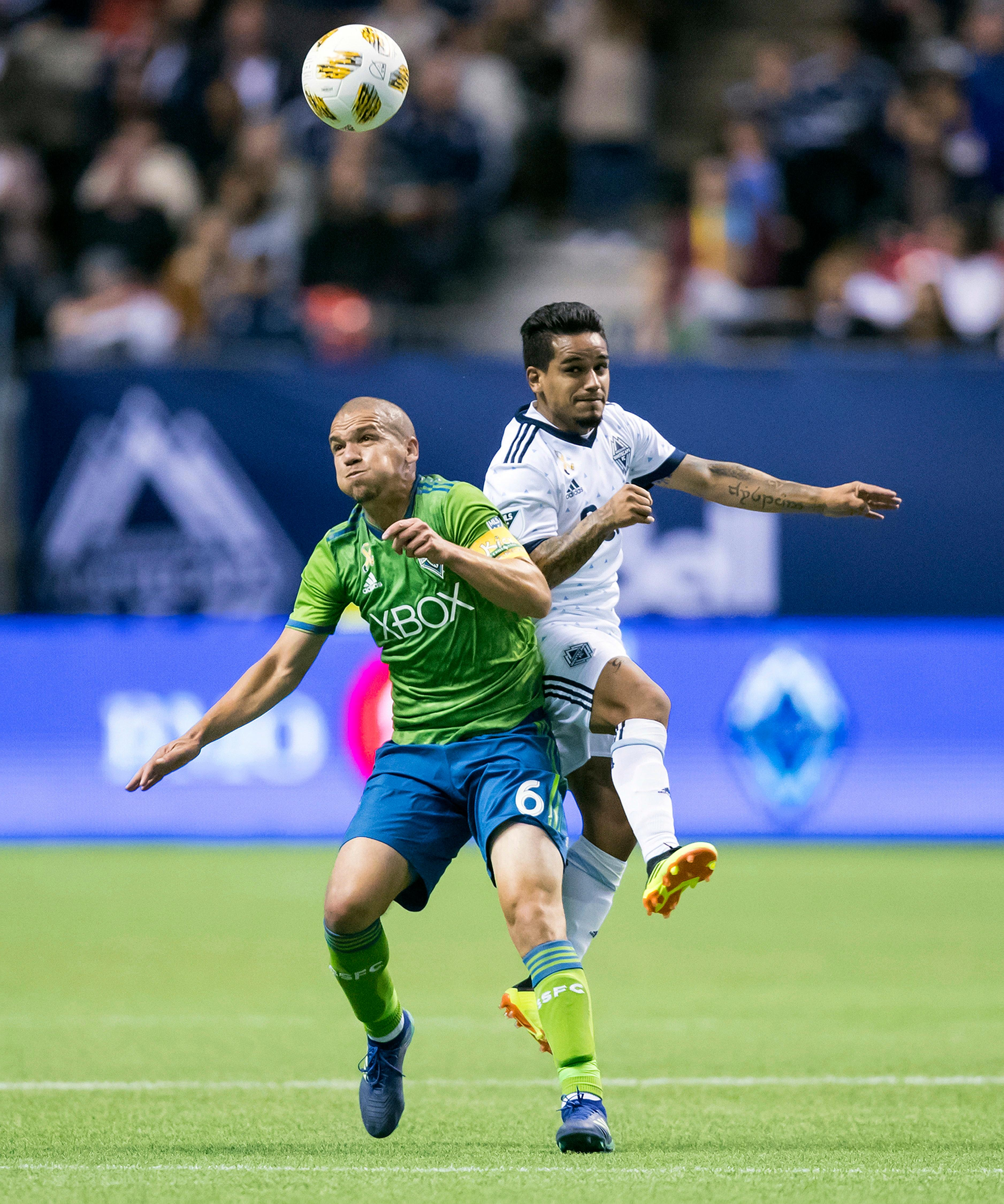 Seattle Sounders' Osvaldo Alonso, left, and Vancouver Whitecaps' Cristian Techera collide during the first half of an MLS soccer match, Saturday, Sept. 15, 2018, in Vancouver, British Columbia. (Darryl Dyck/The Canadian Press via AP)