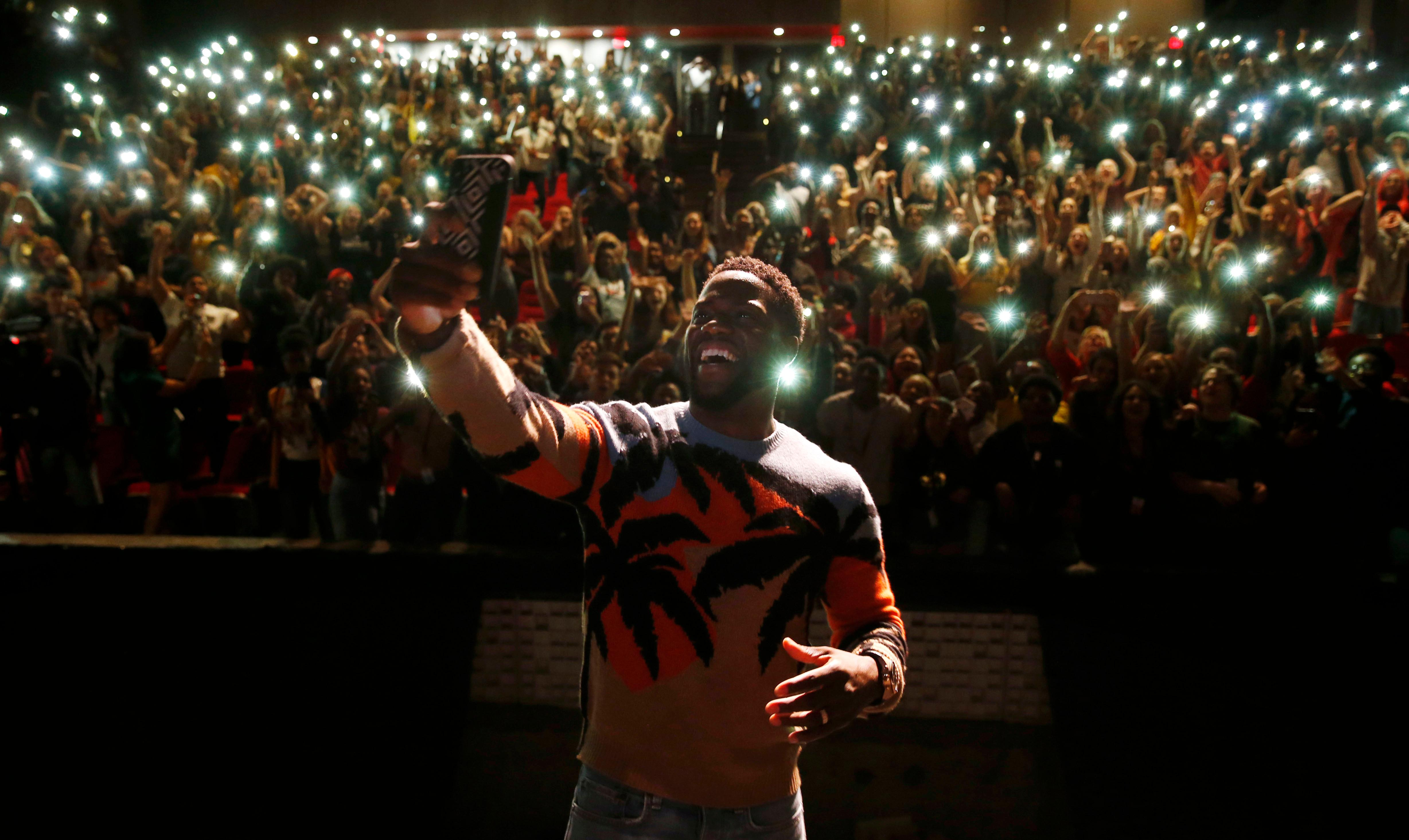 In this Sept. 12, 2018 photo, comedian and actor Kevin Hart films himself with a cellphone after talking to the students at Booker T. Washington High School in Dallas. Hart was named principal for the day. Hart was in town promoting his new movie, Night School. (Vernon Bryant/The Dallas Morning News via AP)