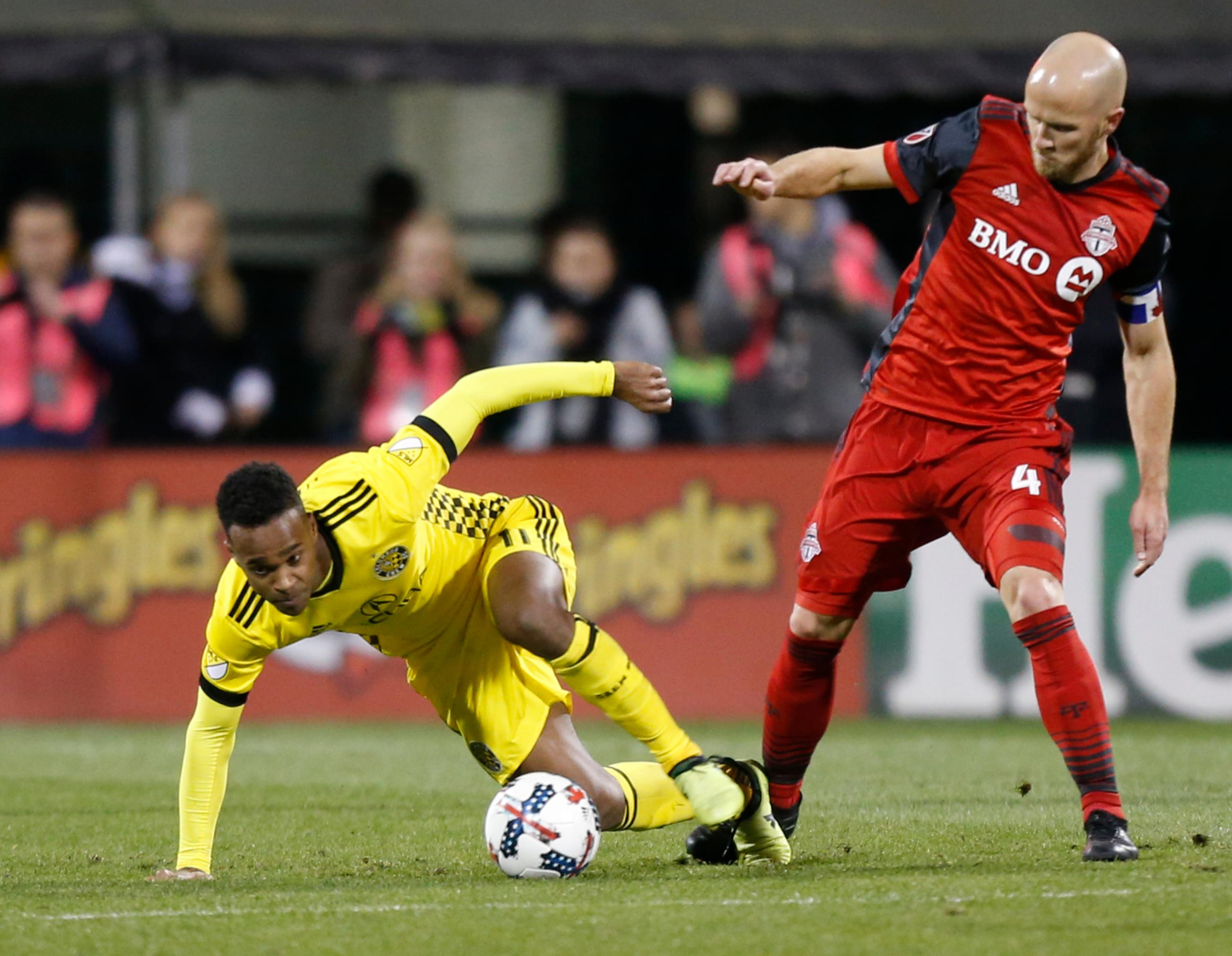 Columbus Crew's Ola Kamara, left, falls the the ground while trying to kick the ball away from Toronto FC's Michael Bradley during the second half of an MLS Eastern Conference championship soccer match Tuesday, Nov. 21, 2017, in Columbus, Ohio. The match ended in a 0-0 tie. (AP Photo/Jay LaPrete)