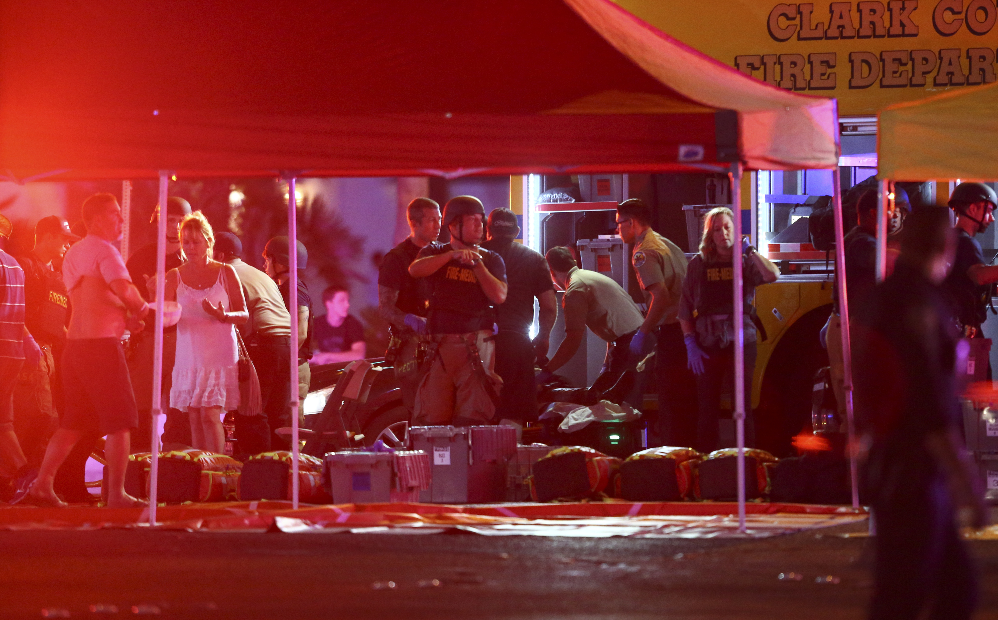 Medics treat the wounded as Las Vegas police respond during an active shooter situation on the Las Vegas Stirp in Las Vegas Sunday, Oct. 1, 2017. Multiple victims were being transported to hospitals after a shooting late Sunday at a music festival on the Las Vegas Strip. (Chase Stevens/Las Vegas Review-Journal via AP)