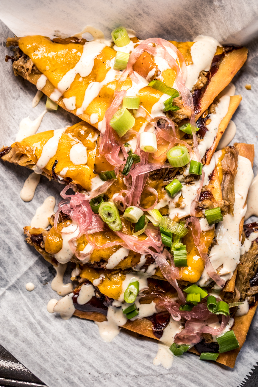 Pulled Pork Flatbread: pulled pork in bourbon BBQ with caramelized onion, sautéed peppers, and cheddar cheese drizzled with ranch and garnished with green onion / Image: Catherine Viox{ }// Published: 5.18.20