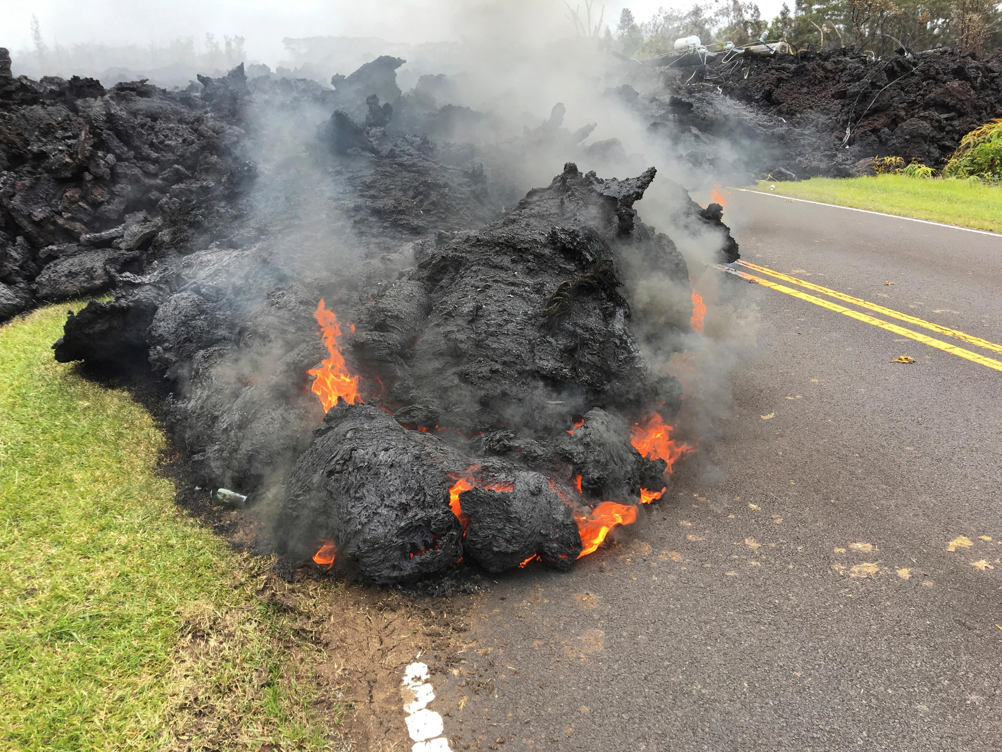 Lava from the Kilauea volcano moves across the road in the Leilani Estates in Pahoa, Hawaii, Saturday, May 5, 2018. Hundreds of anxious residents on the Big Island of Hawaii hunkered down Saturday for what could be weeks or months of upheaval as the dangers from an erupting Kilauea volcano continued to grow. (AP Photo/Marco Garcia)