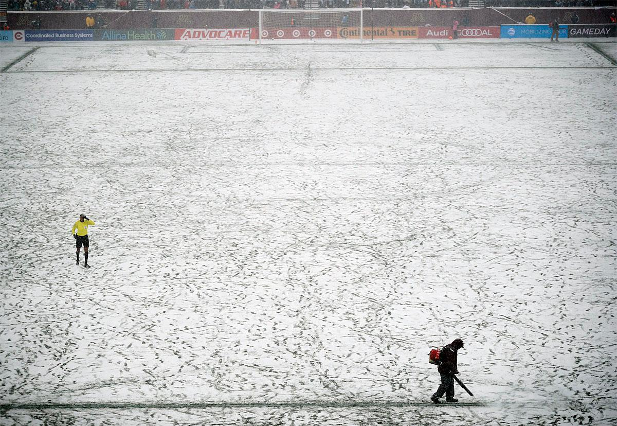 A grounds keeper clears off the lines near the goal during a pause in play in the first half of an MLS soccer game between Atlanta United and Minnesota United, Sunday, March 12, 2017, in Minneapolis, Minn. (Jeff Wheeler/Star Tribune via AP)