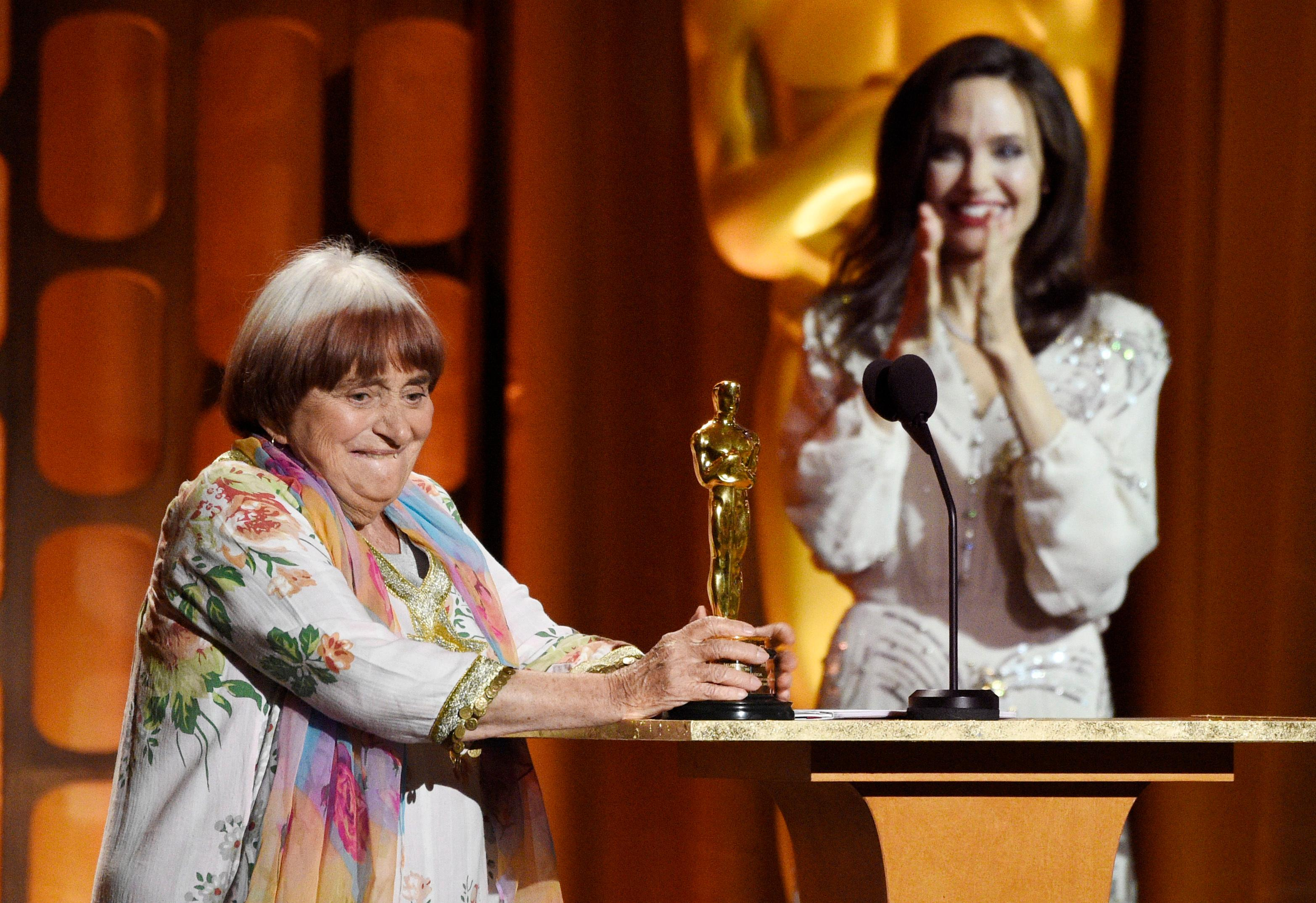 French film director Agnes Varda, left, collects her honorary Oscar onstage as presenter Angelina Jolie applauds at the 2017 Governors Awards at The Ray Dolby Ballroom on Saturday, Nov. 11, 2017, in Los Angeles. (Photo by Chris Pizzello/Invision/AP)