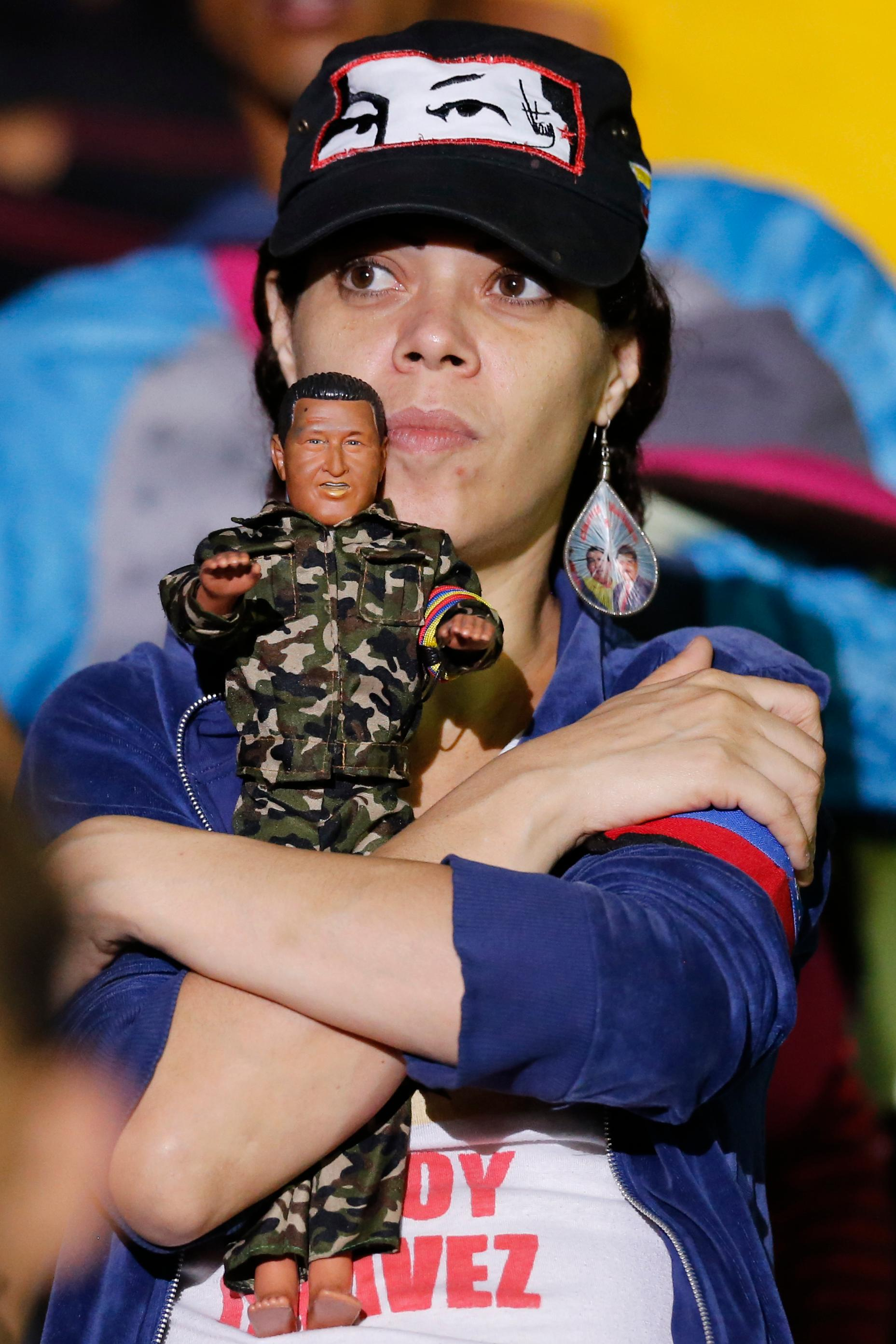 A supporter listens to Venezuela's President Nicolas Maduro, holding a doll of late President Hugo Chavez, at the presidential palace in Caracas, Venezuela, Sunday, May 20, 2018. Election officials say the socialist leader won a second six-year term, while his main rivals are disputing the legitimacy of the vote and calling for a new election. (AP Photo/Ariana Cubillos)