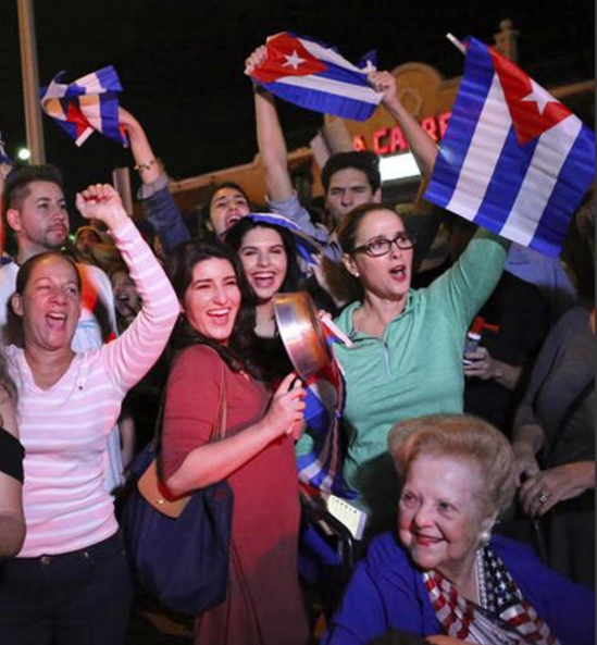 The Cuban community in Miami celebrates the announcement that Fidel Castro died in front La Carreta Restaurant early Saturday, Nov. 26, 2016, in Miami. Within half an hour of the Cuban government's official announcement that former President Fidel Castro had died, Friday, Nov. 25, 2016, at age 90, Miami's Little Havana teemed with life - and cheers. (David Santiago/El Nuevo Herald via AP)