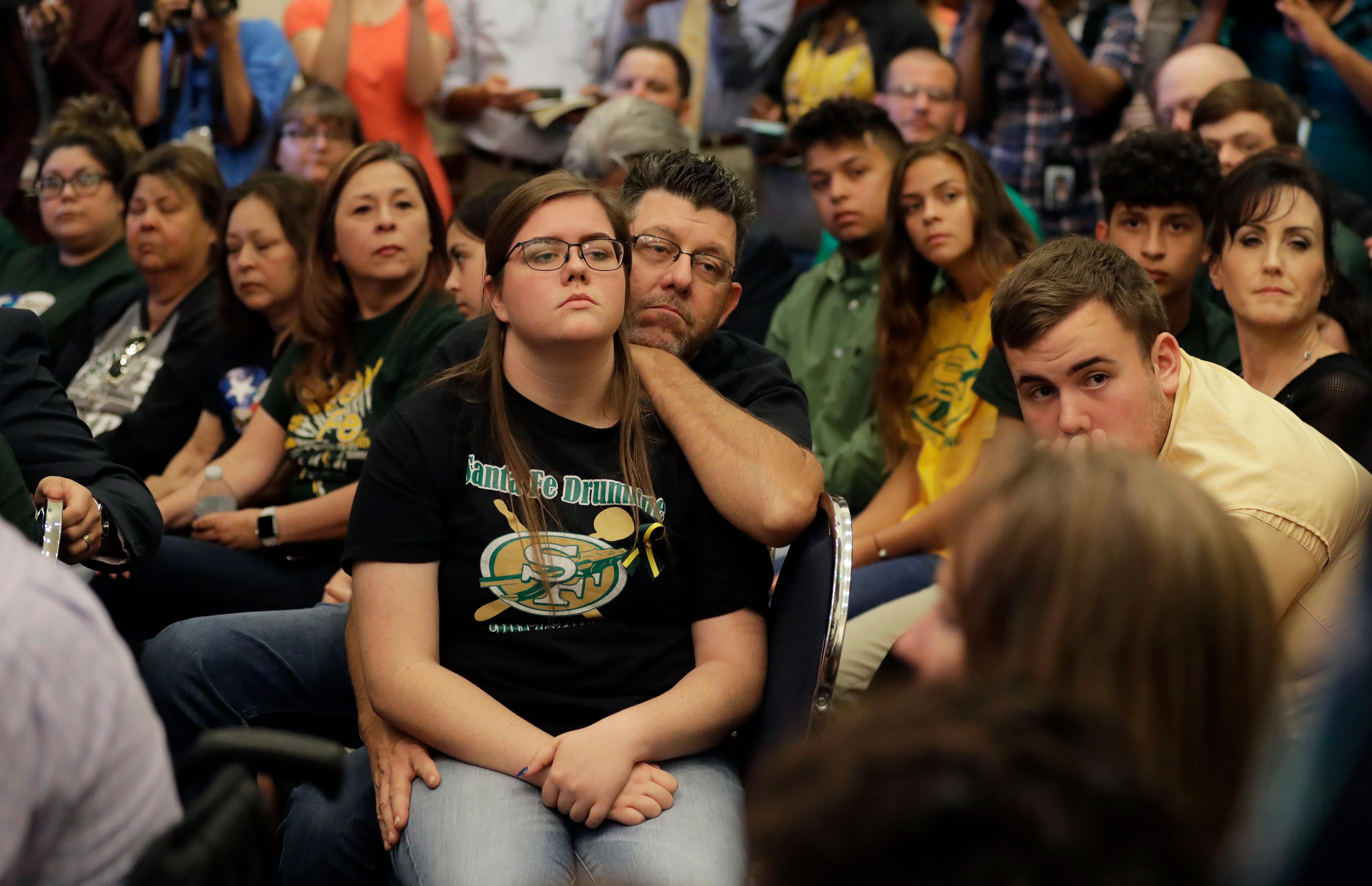 Grace Johnson, a student at Santa Fe High School, center, with her father Steve, and other students, listens during a roundtable discussion in Austin, Texas, Thursday, May 24, 2018, hosted by Texas Gov. Gregg Abbott to address safety and security at Texas schools in the wake of the shooting at Santa Fe, Texas. Thursday's roundtable included victims, students, families and educators from the Santa Fe, Alpine and Sutherland Springs communities. (AP Photo/Eric Gay)